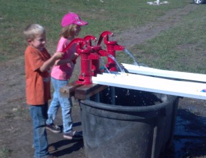 Landon and Jocelyn pump water to race the ducks.